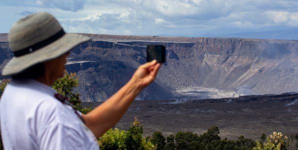 A visitor at Hawaii Volcanoes National Park gets a photo of the expansive crater at Kilauea Caldera. Photography by Baron Sekiya | Hawaii 24/7