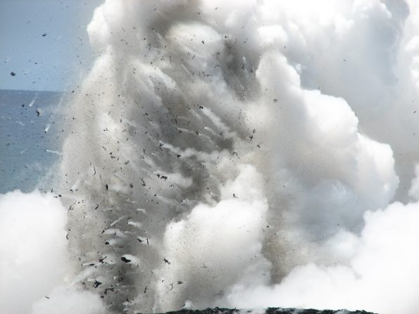 "This telephoto image shows dark fragments of molten and semi-solid lava being blasted upward and outward during a hydrovolcanic explosion at the Waikupanaha ocean entry west of Kalapana in April 2008. Similar explosions are occurring at Kīlauea Volcano's current lower East Rift Zone ocean entry. For more information, please see ""Littoral hydrovolcanic explosions: a case study of lava–seawater interaction at Kilauea Volcano"" (https://volcanoes.usgs.gov/vsc/file_mngr/file-186/Mattox and Mangan_hydrovolcanic explosions.pdf). USGS photo by M. Patrick."