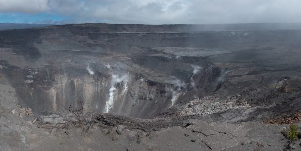 In this panoramic view, Hawaiʻi Volcanoes National Park's Crater Rim Drive (left foreground) disappears into the enormous void created by the collapse of Halema'uma'u and portions of the Kīlauea caldera floor during the dramatic events at the summit of the volcano in May-August 2018. USGS photo by D. Dzurisin.