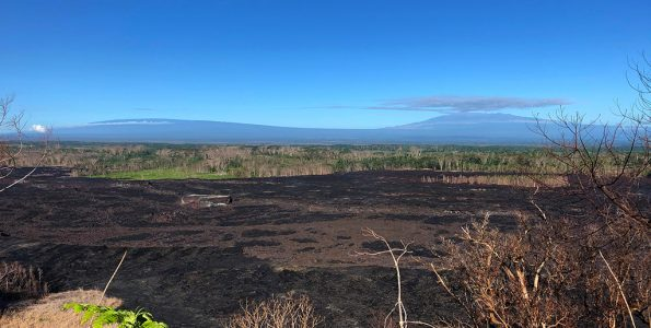 Low sulfur dioxide gas emissions on Kīlauea have resulted in greatly diminished vog (volcanic air pollution) in Hawaii, giving rise to spectacular views on the island. Here, looking across the field of lava erupted from Kīlauea's lower East Rift Zone this past summer, the shield-shaped profiles of Mauna Loa (left) and Mauna Kea (right) can be clearly seen in the far distance. Photo taken Wednesday, October 10, 2018 courtesy of U.S. Geological Survey