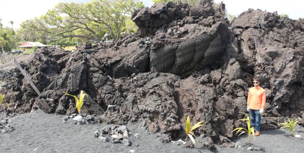 """HVO geologists (one shown here for scale) examined Kīlauea Volcano's 2018 lava flow near Isaac Hale Beach Park on March 29. This part of the lower East Rift Zone fissure 8 flow is mostly """"toothpaste lava""""—an informal name for secondary spiny pāhoehoe lava that oozed out from the stalled primary 'a'ā flow that reached the coast. This lobe, classic toothpaste lava, is about 3-4 m (9–13 ft) thick and about 70 m (76–77 yds) long. USGS photo by M. Patrick."""